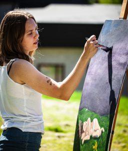 Deltagare står och målar akryl vid ett staffli utomhus i solsken